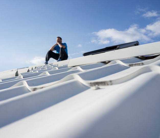 Man on the top of house roof thinking