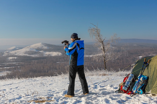 A man at the top of the mountain looks through binoculars. he stands near the tent in the morning on