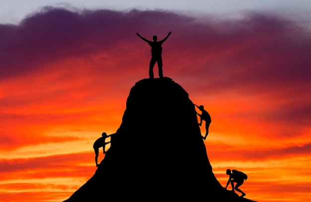 Man on top of the mountain and the other people to climb up. sport and active life.