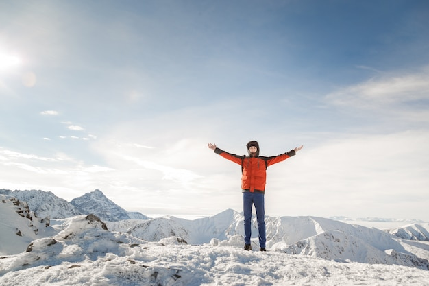Man on the top of the world raised his hands proud of his achievements