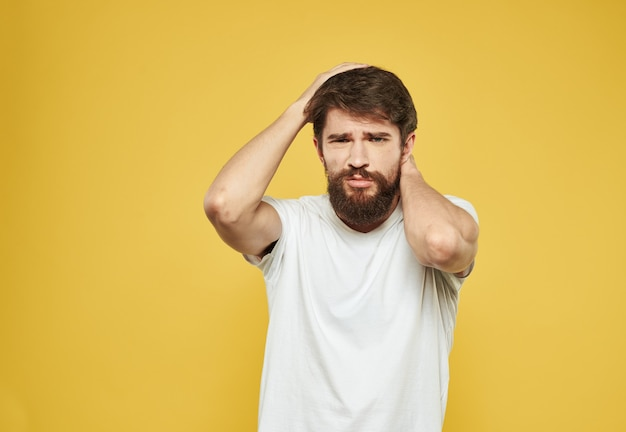 A man touches his face with his hands puzzled look yellow background cropped view. high quality photo