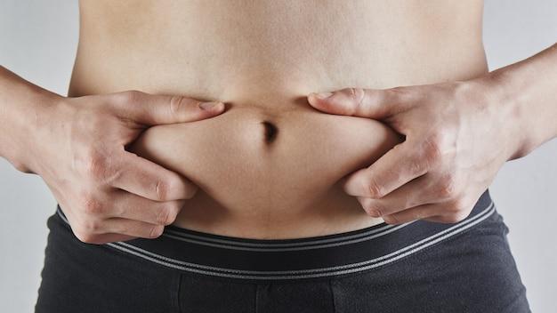 남자는 그의 뚱뚱한 배꼽 근접 촬영, 비만, 남성 체중 감량 및 다이어트 개념을 만집니다.