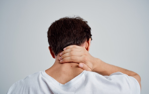 Man touches his neck with his hand injury pain osteochondrosis problems with the spine