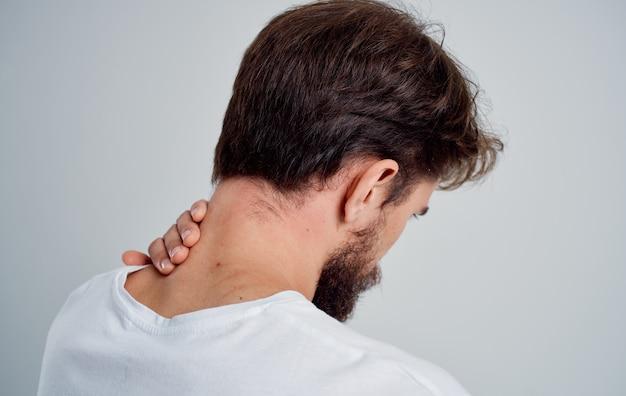 Мужчина трогает шею рукой, травма, боль, остеохондроз, проблемы с позвоночником.