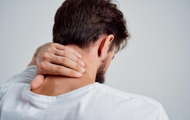 남자는 손 부상으로 목을 만집니다. 척추의 골 연골 증 문제