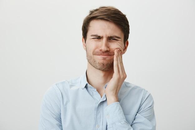 Мужчина трогает щеку и морщится от боли от зубной боли