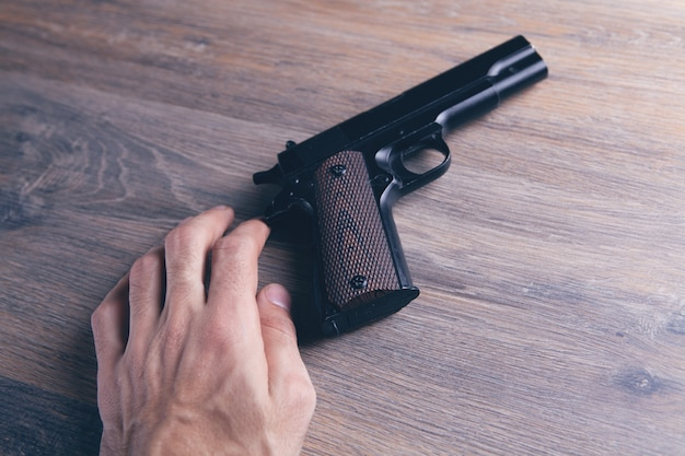 나무 테이블에 총을 만지는 남자