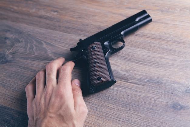Man touching gun on wooden table