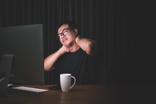 Мужчина трогает его шею из-за боли от работы на компьютере