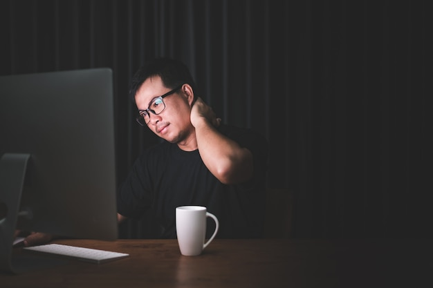 コンピューターでの作業による痛みのために首に触れる男
