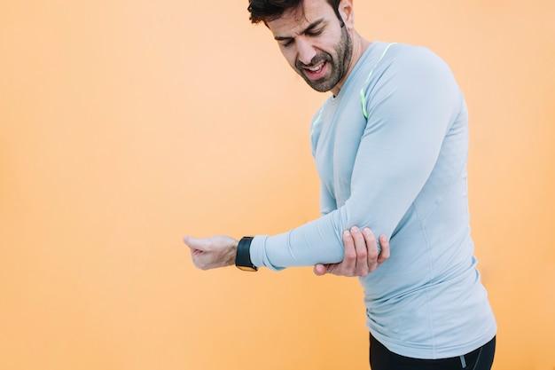 Man touching hurting elbow