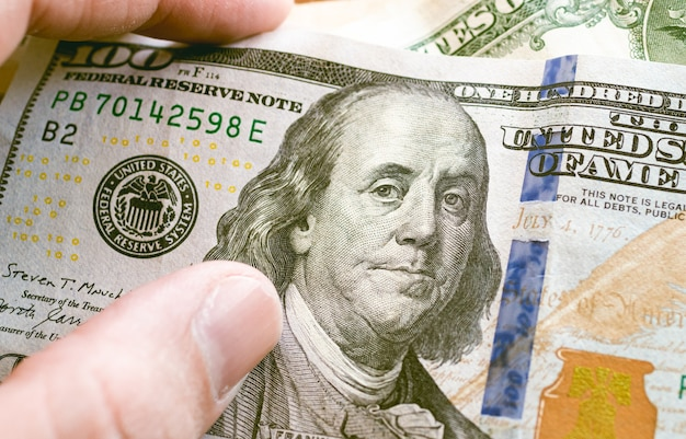 A man touching a one hundred dollar bill from the united states in close up photo