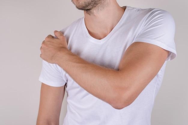 Человек трогает плечо на изолированном сером фоне