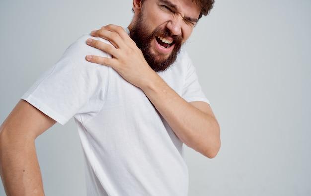 Человек трогает плечо с дискомфортным вывихом руки белой футболке