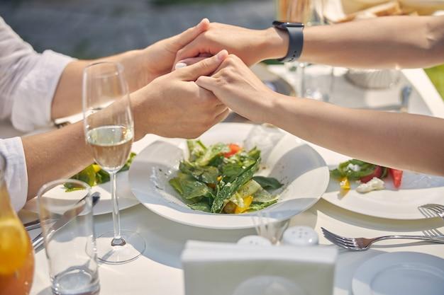 레스토랑 테이블에서 데이트하는 동안 파트너의 손을 만지는 남자