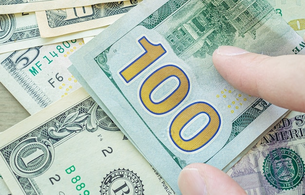 A man touching a us hundred dollar bill in close up photo