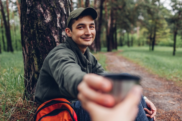 Man tourist giving cup of hot tea to his friend in spring forest camping, traveling