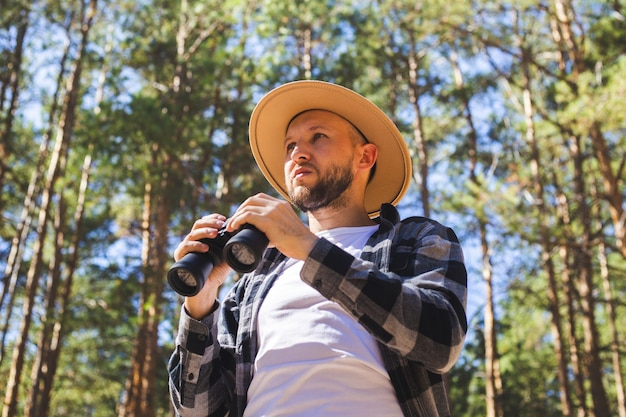 Man tourist in a hat and gray plaid shirt looks through binoculars.