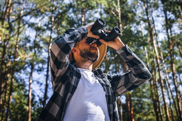 Man tourist in a hat and a plaid shirt looks through binoculars in the forest.