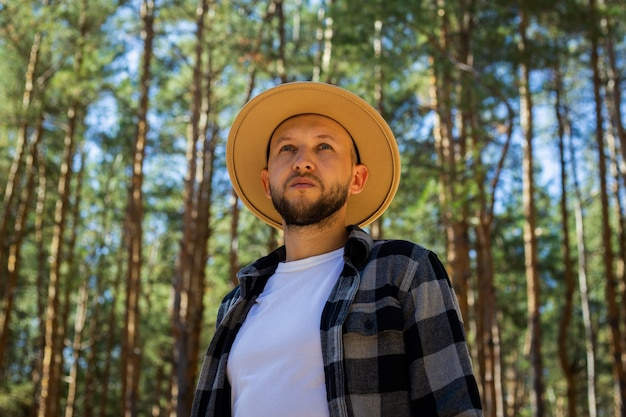 Man tourist in hat and plaid shirt in the woods.