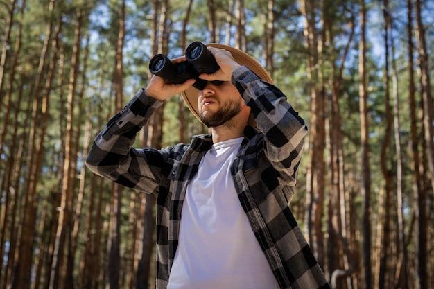 帽子と格子縞のシャツを着た男性観光客が森の中の双眼鏡を通して見ています。
