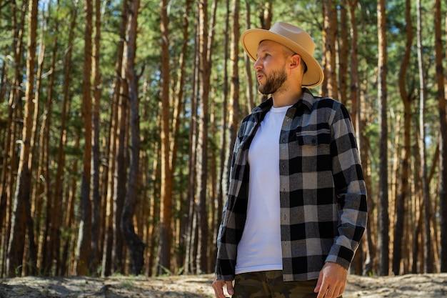 Турист человек в шляпе и клетчатой рубашке в лесу.