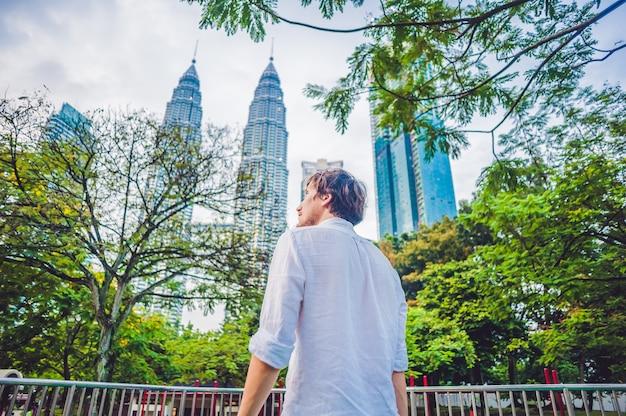 マレーシアの男性観光客がペトロナスツインタワーを見る