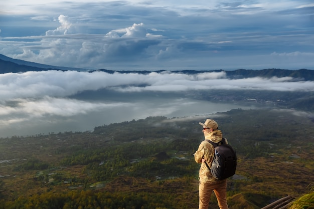 Man tourist looks at the sunrise on the volcano batur on the island of blai in indonesia. hiker man with backpack travel on top volcano, travel concept