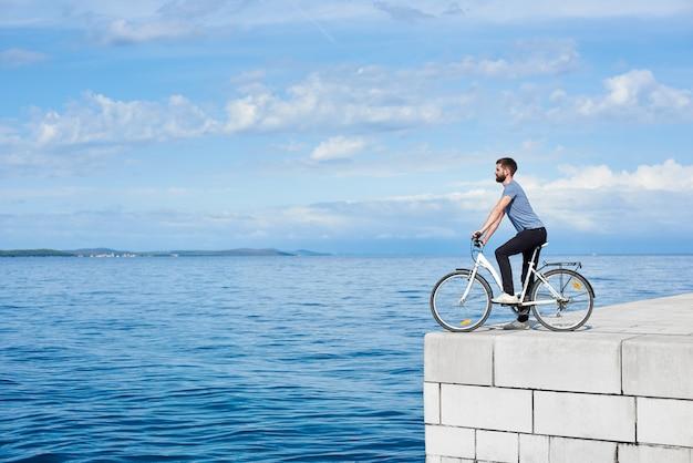 Человек турист на велосипеде на высоком мощеном каменном тротуаре