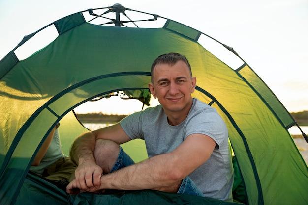 Турист человек сидит внутри палатки лагеря. мужчина проводит отпуск с палаткой у озера.