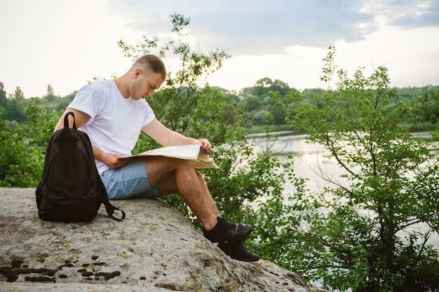Мужчина-турист, сидящий на камне у реки, читает карту.