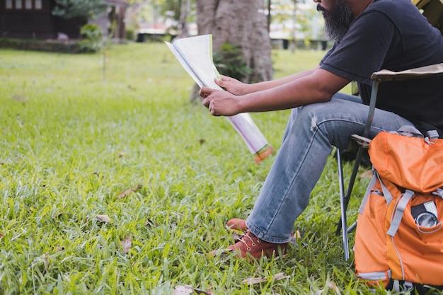 男観光客が椅子に座って、森のキャンプ場でテントの前で地図を読む