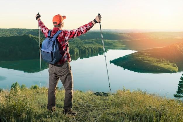 素晴らしい自然の景色に立ち向かう男の観光客。屋外のバックパックワンダーラスト休暇での旅行ライフスタイルアドベンチャーコンセプトハイキング。
