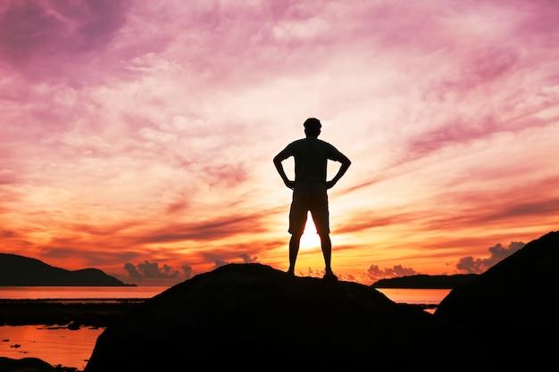 열대 바다에서 돌에 서서 일출 동안 경치를 즐기는 남자 관광