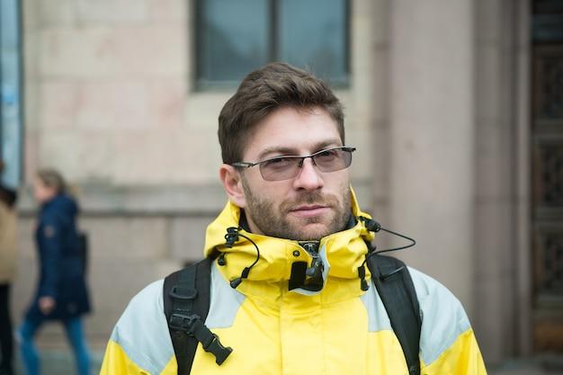 男性の観光客は、寒い気候条件のために暖かい保護服を着ます。観光旅行者のコンセプト。すぐに使える観光井戸設備は、スカンジナビアまたは北欧の国を探索します。都市の背景の観光客。
