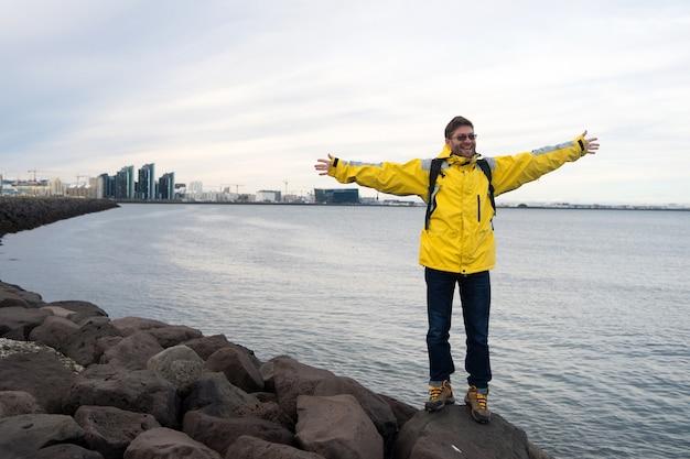男性の観光客は、寒い気候条件のために暖かい保護服を着ます。観光用の井戸設備は、スカンジナビアまたは北欧の国を探索する準備ができています。観光旅行者のコンセプト。海の背景の観光客。