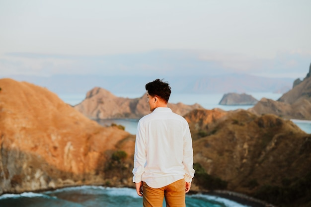 Man tourist in white dress standing on top of padar island with blurry background of sea and hill