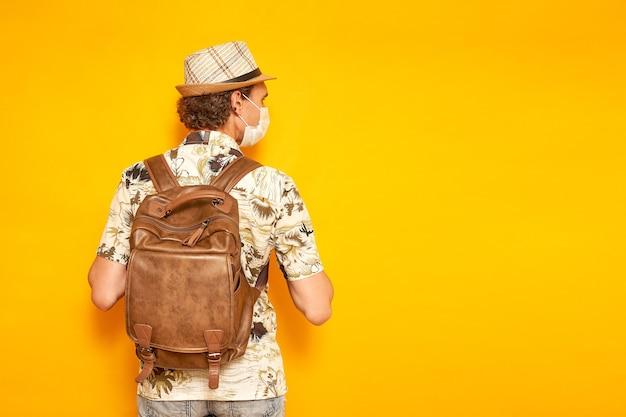 医療マスクのバックパックを持つ男の観光客は彼の背中を立って目をそらします孤立した黄色の背景