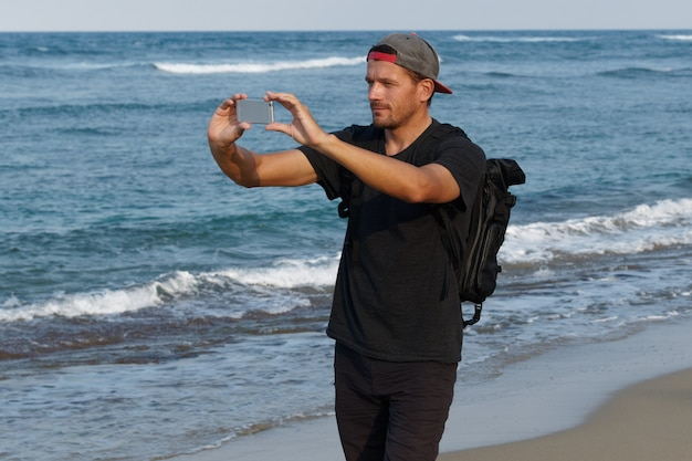 Man tourist with backpack using cell phone to take photo, standing on a beach.