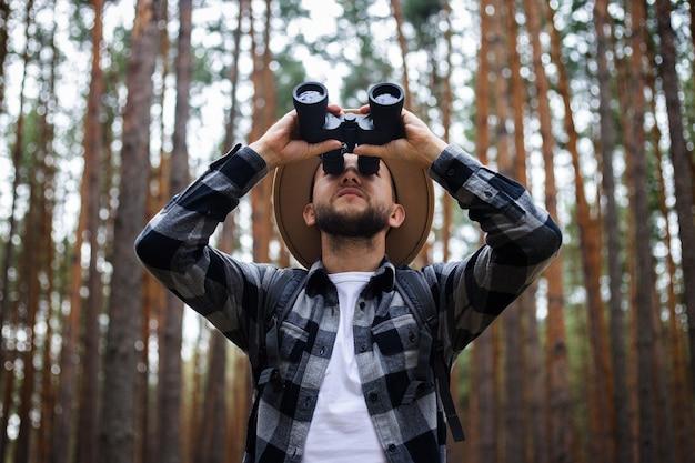 숲에서 하이킹하는 동안 쌍안경으로 남자 관광. 산이나 숲에서 하이킹.