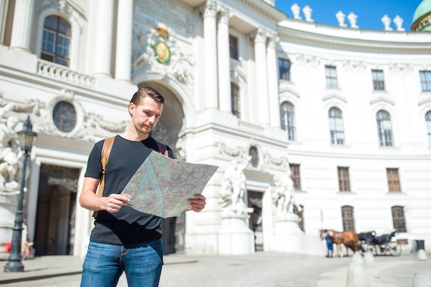Man tourist with a city map and backpack in europe street, caucasian boy looking with map of european city,
