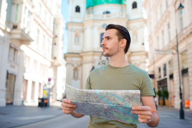 Man tourist with a city map and backpack in europe street.