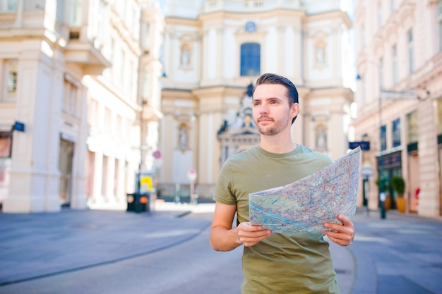 Man tourist with a city map in europe street.