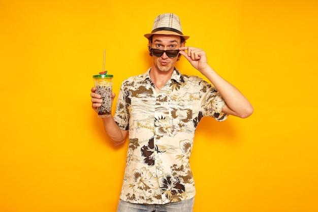 열대 음료를 손에 들고 있는 남자 관광객은 선글라스에 고립된 노란색 배경 복사 공간을 낮췄다