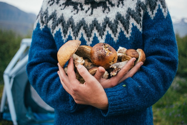 Man in traditional blue wool sweater with ornaments stands on camping ground in mountains, holds in arms pile of delicious and organic, fresh natural mushrooms from forest