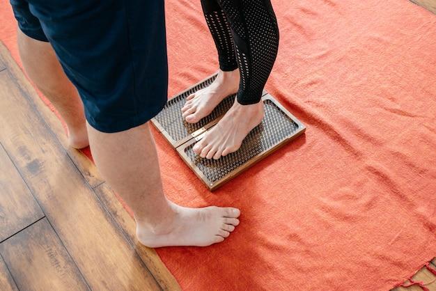 Мужчина-тренер помогает женщине стоять на доске садху-йоги, босиком на гвоздях