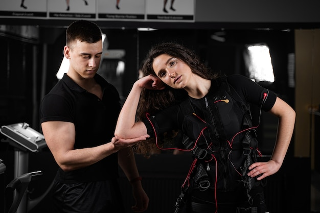 Man trainer trains a girl in an ems suit in the gym