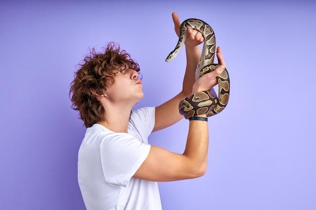 뱀을 훈련하는 남자와 즐거움, 그와 함께 연주하는 젊은 백인 남자, 보라색 배경에 고립 된 포즈. 측면보기
