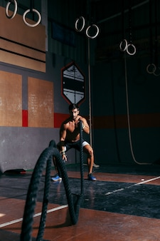 Man training crossfit with rope