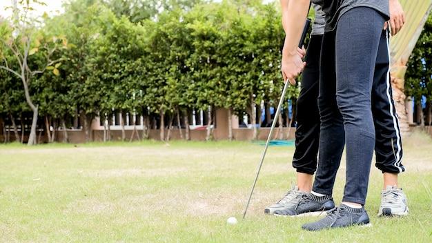 Man training golf player in garden